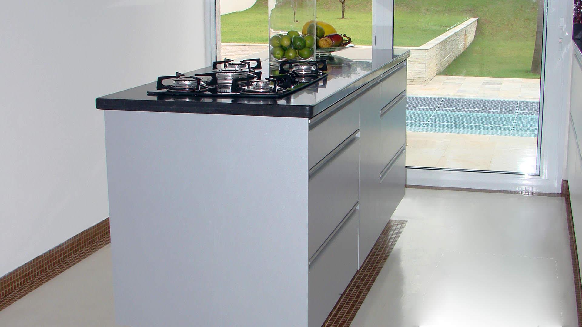 cozinha planejada com ilha e cooktop de vidro